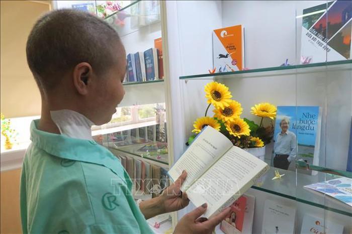 Bệnh nhân ung thư đọc sách tìm hiểu về ung thư.