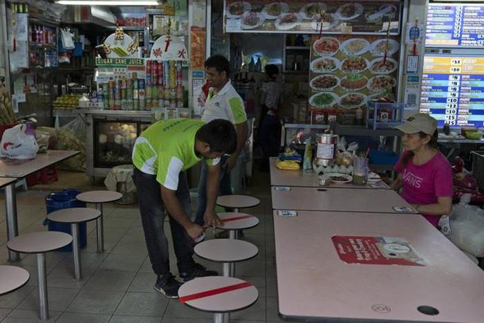 Nhân viên đánh dấu những ghế không được ngồi trong một trung tâm thực phẩm tại Singapore